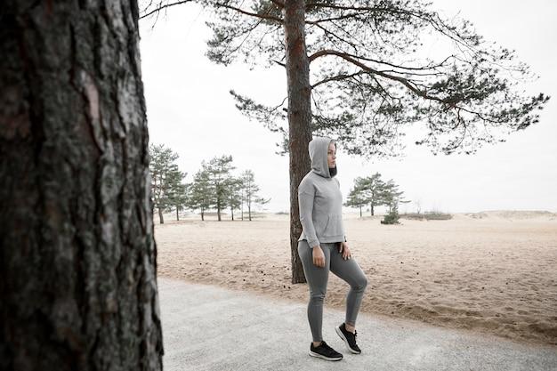 Foto de corpo inteiro de uma elegante corredora europeia aquecendo o corpo antes do treinamento cardiovascular ao ar livre, usando tênis, leggings e moletom elegantes, parada em uma trilha pavimentada na floresta ou no parque