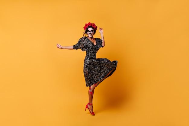 Foto de corpo inteiro de uma encantadora mulher ousada em um lindo vestido com maquiagem para o halloween, dança incendiária de salto alto