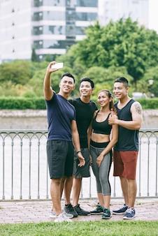 Foto de corpo inteiro de uma equipe de quatro esportes tirando uma selfie ao ar livre