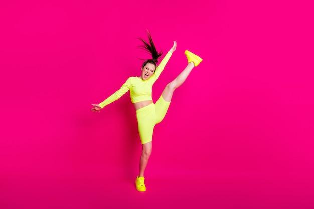 Foto de corpo inteiro de uma esportista pulando alto gritando, mantendo a perna erguida isolada no fundo de cor rosa brilhante
