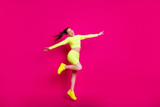 Foto de corpo inteiro de uma esportista pulando e rindo alegremente apontando para copyspace isolado em um fundo de cor rosa vibrante