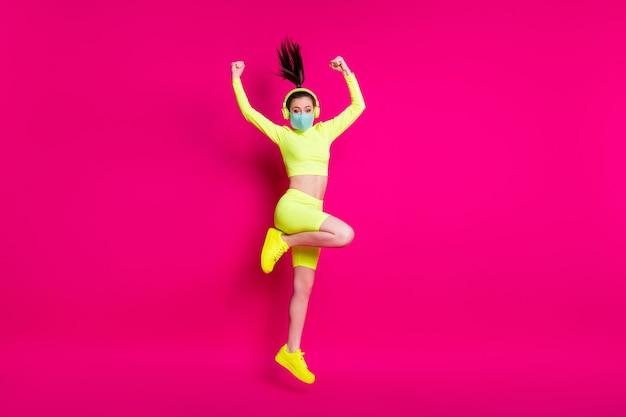 Foto de corpo inteiro de uma esportista pulando, mostrando mãos fortes usando fones de ouvido de máscara, isolados em um fundo de cor fúcsia brilhante
