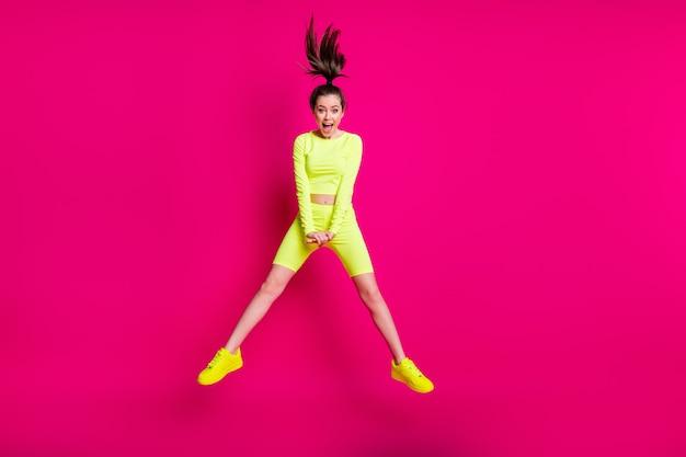 Foto de corpo inteiro de uma esportista pulando rindo usando um rabo de cavalo esportivo isolado em um fundo de cor rosa brilhante
