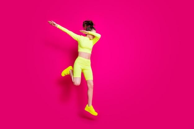 Foto de corpo inteiro de uma esportista pulando usando tênis esportivos amarelos, mostrando o exagero isolado em um fundo de cor rosa viva
