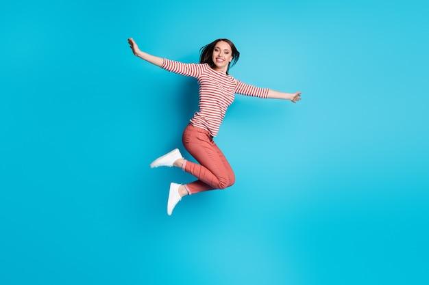 Foto de corpo inteiro de uma garota adorável e animada pulando de mãos dadas imagine que ela voa como um pássaro usando roupas bonitas isoladas sobre fundo de cor azul