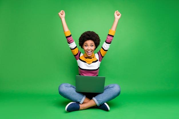 Foto de corpo inteiro de uma garota afro americana louca e funky trabalhar laptop sentar pernas cruzadas ganhar coworking negócio gritar uau omg levantar os punhos usar jeans jeans engraxar roupa