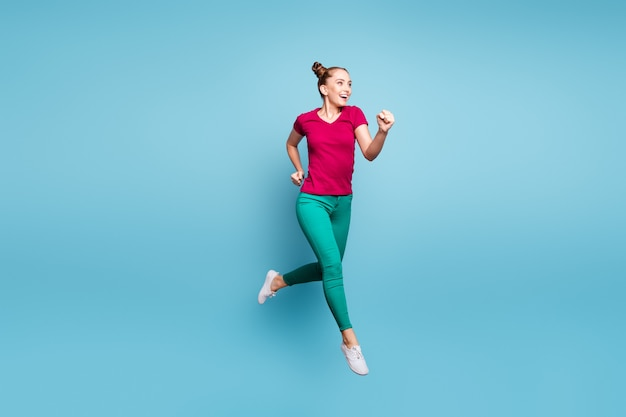 Foto de corpo inteiro de uma garota alegre apressada e urgente usando calça calça verde, correndo, pulando isolada na parede azul pastel
