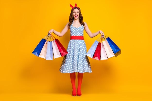 Foto de corpo inteiro de uma garota animada segurando sacolas de compras em fundo amarelo