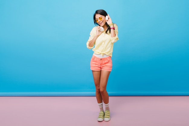 Foto de corpo inteiro de uma garota bronzeada bem torneada em shorts rosa dançando com prazer. pegando uma mulher europeia de cabelos escuros em sapatos amarelos, ouvindo música em fones de ouvido brancos.