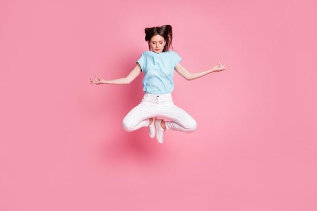 Foto de corpo inteiro de uma garota calma e pacífica, pular ioga, meditar, usar roupas brancas azuis isoladas de fundo de cor pastel