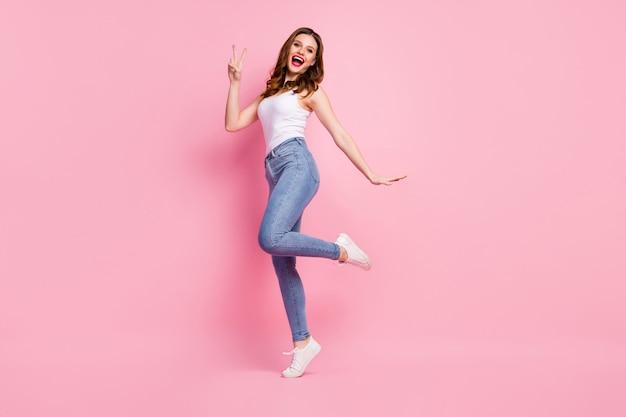 Foto de corpo inteiro de uma garota cândida fazendo vsign posando