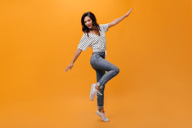 Foto de corpo inteiro de uma garota de jeans e camiseta em fundo laranja