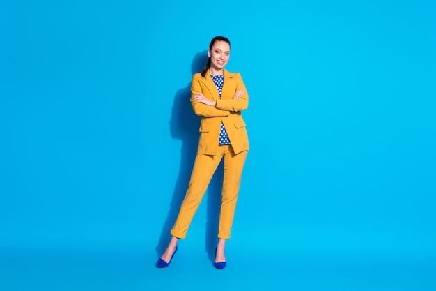 Foto de corpo inteiro de uma garota elegante encantadora muito confiante em um terno brilhante, segurando os braços cruzados, isolado de fundo azul