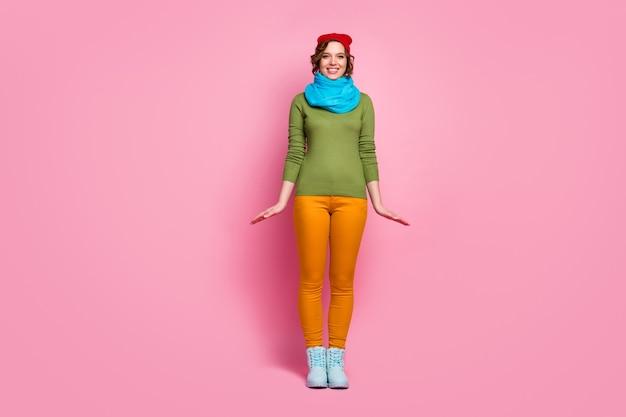 Foto de corpo inteiro de uma garota encantadora e satisfeita curtindo uma viagem de inverno, uma viagem de inverno, vestindo uma roupa casual isolada sobre uma parede de cor pastel