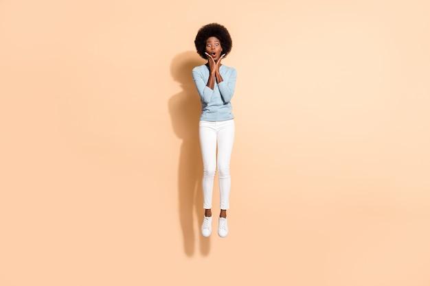 Foto de corpo inteiro de uma garota encaracolada chocada e surpresa com pele escura pulando alto tocando o rosto com as mãos isoladas em um fundo de cor bege