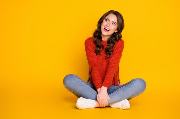 Foto de corpo inteiro de uma garota excitada e cândida sentar pernas cruzadas no chão olhar copyspace desfrutar alegrar-se anúncios vendas vestir suéter jeans isolado sobre fundo de cor brilhante
