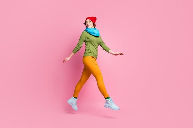 Foto de corpo inteiro de uma garota jovem alegre e fofa pule, vá olhar copyspace sinta um sonho com descontos de primavera, use suéter de calças isolado sobre parede cor de rosa