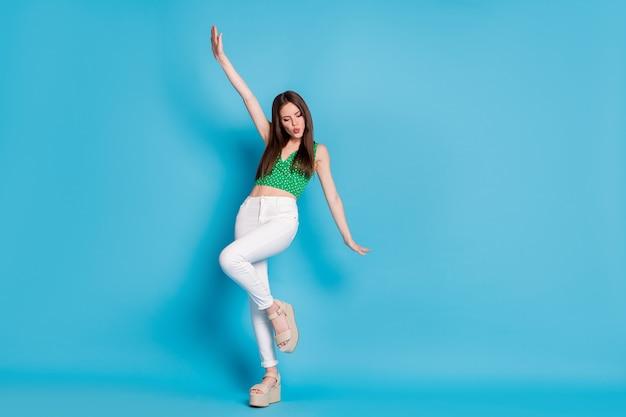 Foto de corpo inteiro de uma garota legal e sincera curtindo, alegre-se, dança, discoteca, levante a mão, use a camiseta regata isolada sobre o fundo de cor azul