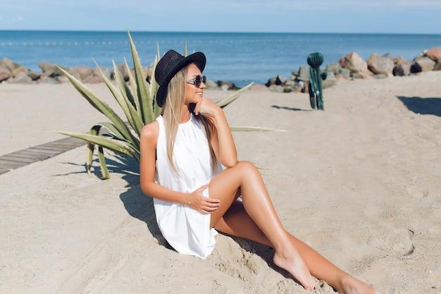 Foto de corpo inteiro de uma garota loira e bonita com cabelo comprido está sentado na praia perto de cacto no fundo. ela está sorrindo para o lado.