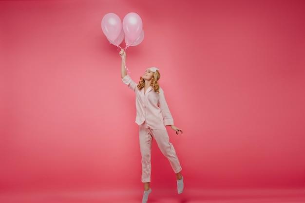 Foto de corpo inteiro de uma garota loira entusiasmada posando com balões. retrato interior de senhora alegre em máscara de dormir, na ponta dos pés em seu aniversário.