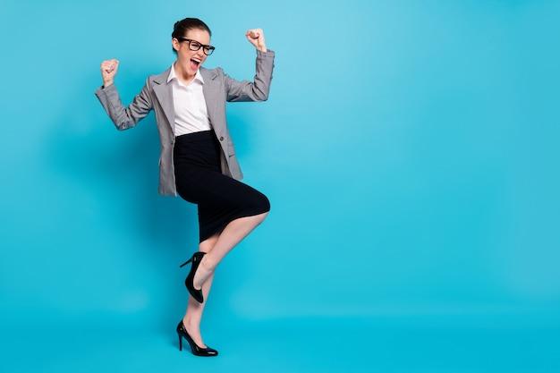 Foto de corpo inteiro de uma garota maluca que o advogado levanta os punhos gritando e usa um blazer preto cinza com salto alto isolado fundo de cor azul