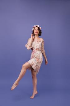 Foto de corpo inteiro de uma garota maravilhosa com vestido de verão. mulher jovem bem vestida em círculo de flores dançando.