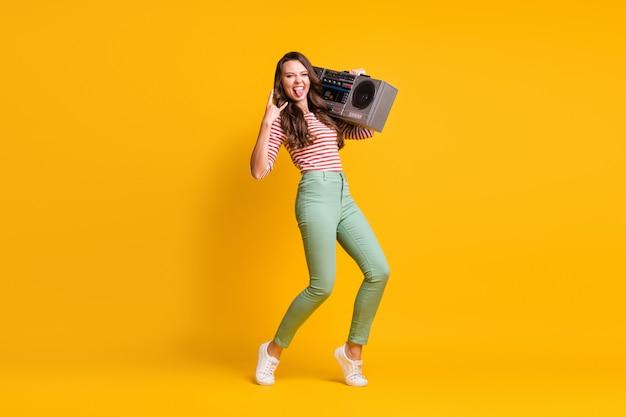 Foto de corpo inteiro de uma garota ouvindo um boombox retrô mostrando chifres de metal pesado isolado em um fundo de cor amarela vibrante