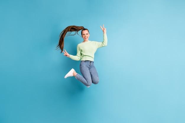Foto de corpo inteiro de uma garota pulando com cabelo comprido mostrando o sinal de v com as duas mãos isoladas em um fundo de cor azul viva