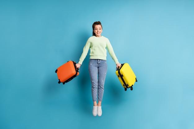 Foto de corpo inteiro de uma garota pulando, mantendo malas coloridas antes do voo no aeroporto, isolada em um fundo de cor azul viva