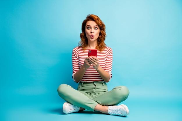 Foto de corpo inteiro de uma garota surpresa, sente-se com as pernas cruzadas, use o telefone celular, leia as informações da mídia social.