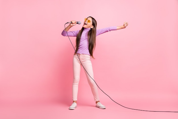 Foto de corpo inteiro de uma garotinha cantando música no microfone usando uma calça jumper roxa isolada sobre um fundo de cor pastel