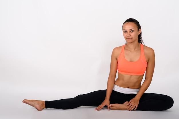 Foto de corpo inteiro de uma jovem asiática esticando a perna direita enquanto está sentada no chão em um espaço em branco
