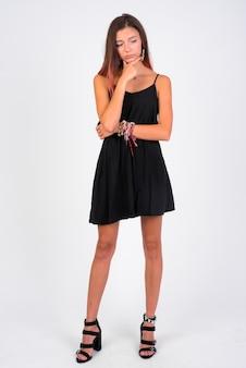 Foto de corpo inteiro de uma jovem bonita pensando enquanto usa um vestido preto