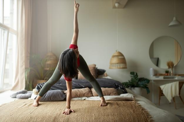 Foto de corpo inteiro de uma jovem descalça com corpo atlético flexível em pé no tapete em parivrtta prasarita padottanasana, fazendo ioga, melhorando a digestão, fortalecendo isquiotibiais e coxas