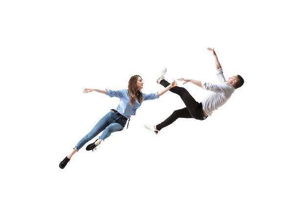 Foto de corpo inteiro de uma jovem e um homem pairando no ar