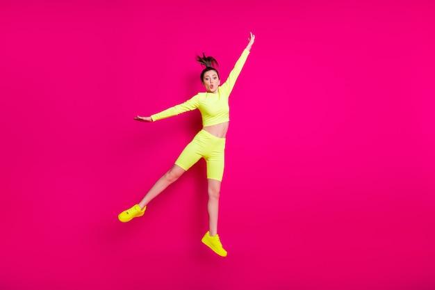 Foto de corpo inteiro de uma jovem esportista pulando alto vestindo tênis esportivos amarelos isolados em um fundo de cor rosa vibrante