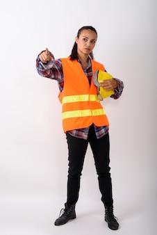 Foto de corpo inteiro de uma jovem mulher asiática da construção civil em pé, segurando um capacete e apontando o dedo contra o espaço em branco