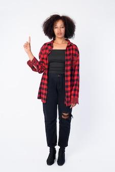 Foto de corpo inteiro de uma jovem mulher bonita hipster africana apontando para cima