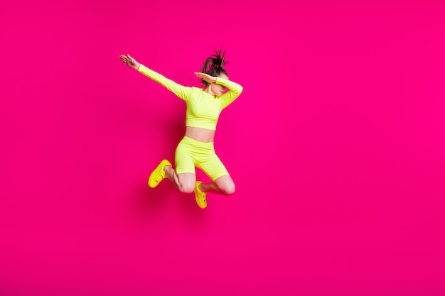 Foto de corpo inteiro de uma jovem saltitante vestindo roupas esportivas amarelas, mostrando o hype isolado em um fundo de cor rosa brilhante