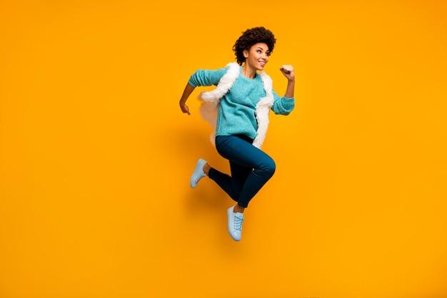 Foto de corpo inteiro de uma linda garota afro-americana louca com descontos em corrida de salto usar suéter azul-esverdeado branco calças azuis elegantes e tênis da moda isolado sobre a parede amarela brilhante