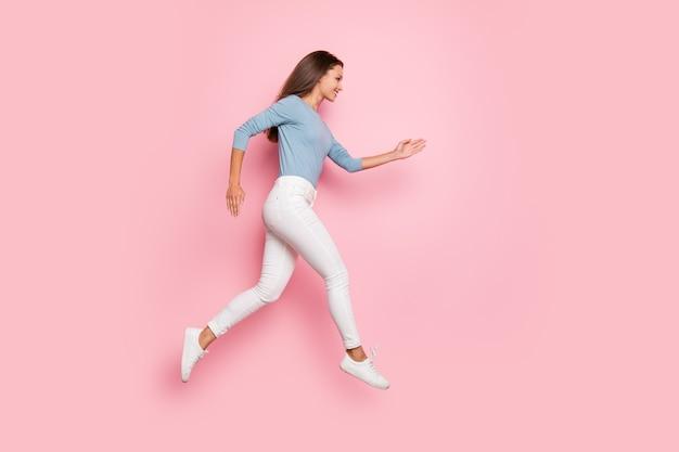 Foto de corpo inteiro de uma linda garota concentrada correndo para o espaço vazio em um suéter azul para vendas isoladas de fundo de cor pastel