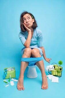 Foto de corpo inteiro de uma linda jovem asiática relaxada ponderando sobre algo enquanto faz xixi no vaso sanitário com a calcinha puxada para baixo nas pernas isoladas sobre a parede azul
