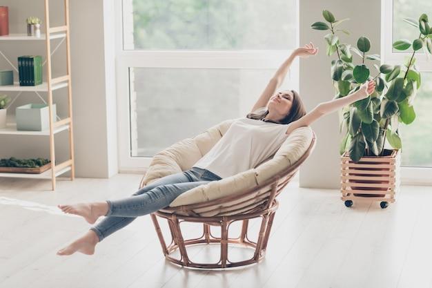 Foto de corpo inteiro de uma linda jovem sentada em uma poltrona de vime, braços esticados e vestindo roupas de estilo casual em um apartamento em casa