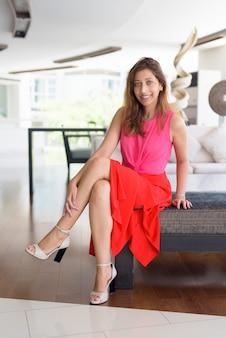 Foto de corpo inteiro de uma linda mulher hispânica feliz sentada em casa dentro de casa