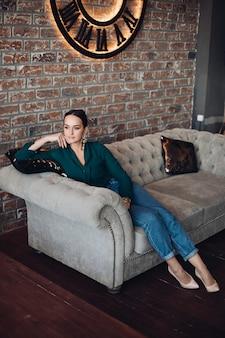 Foto de corpo inteiro de uma linda mulher morena em roupas casuais elegantes e saltos altos relaxando no sofá clássico com almofadas e olhando para longe. o quarto é em estilo loft.