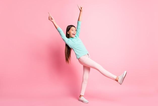 Foto de corpo inteiro de uma menina brincalhona apontando para cima com dedos dando um passo à frente sorrindo isolada em um fundo de cor rosa