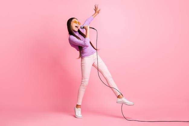 Foto de corpo inteiro de uma menina pequena cantando música no microfone usando calças suéter violeta isoladas sobre fundo de cor pastel