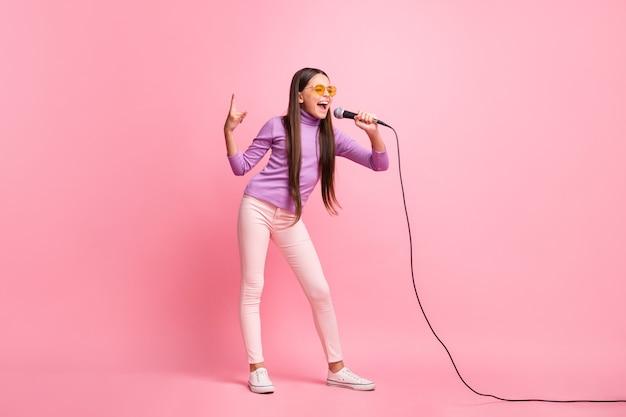Foto de corpo inteiro de uma menina pequena cantando música no microfone usando calças suéter violeta isoladas sobre um fundo de cor pastel