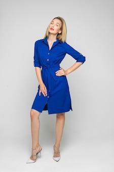 Foto de corpo inteiro de uma mulher adulta na moda com cabelo loiro usando um vestido formal azul brilhante com botões