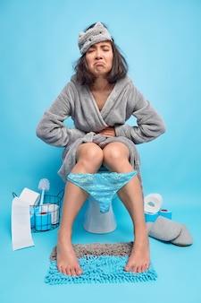 Foto de corpo inteiro de uma mulher asiática morena descontente com cólicas abdominais